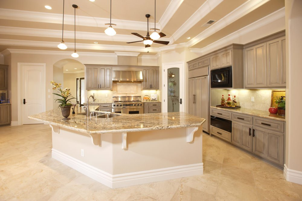 Large kitchen with elegant floors, walls and ceiling lighted by pendant lights. There's a massive center island with marble countertop.