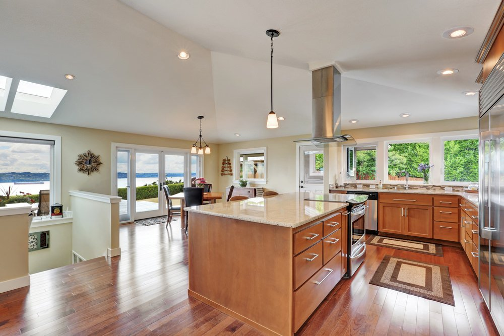 Spacious dine-in kitchen surrounded with glass windows that overlook a serene outdoor view. It has wood cabinetry and kitchen island fitted with a built-in range and drawers with chrome pulls.