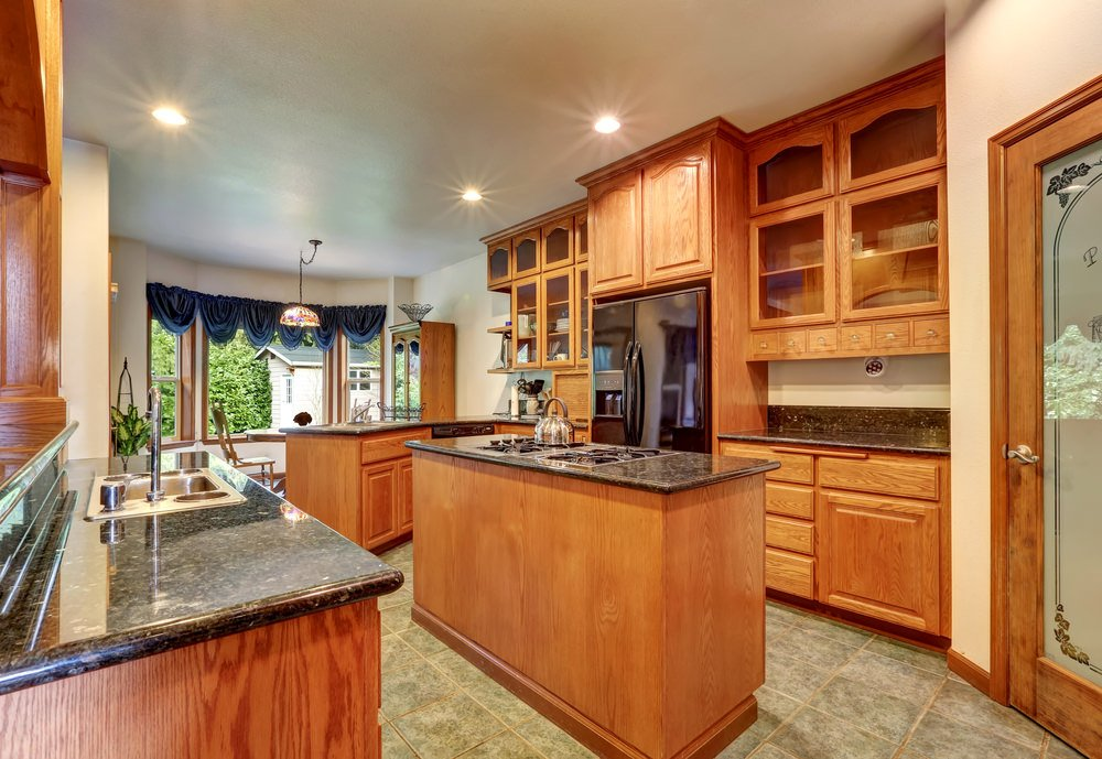 This kitchen with walnut finished cabinetry and tiles flooring is so eye-catching. The counters are topped by granite. There's a narrow center island as well.