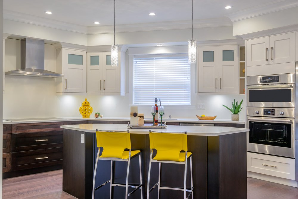 This kitchen features white walls matching the white cabinetry and kitchen countertops. The pendant lights look so lovely.