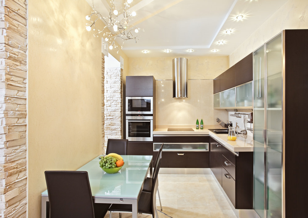 Charming kitchen illuminated by a fancy chandelier and recessed ceiling lights. It has L-shaped stained wood cabinetry that matches with the dining chairs surrounding a metal table topped with frosted glass.