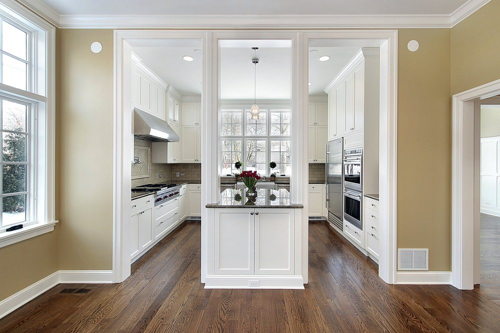 Large and stylish U-shaped kitchen featuring a hardwood flooring and white cabinetry and counters lighted by recessed and pendant lights.