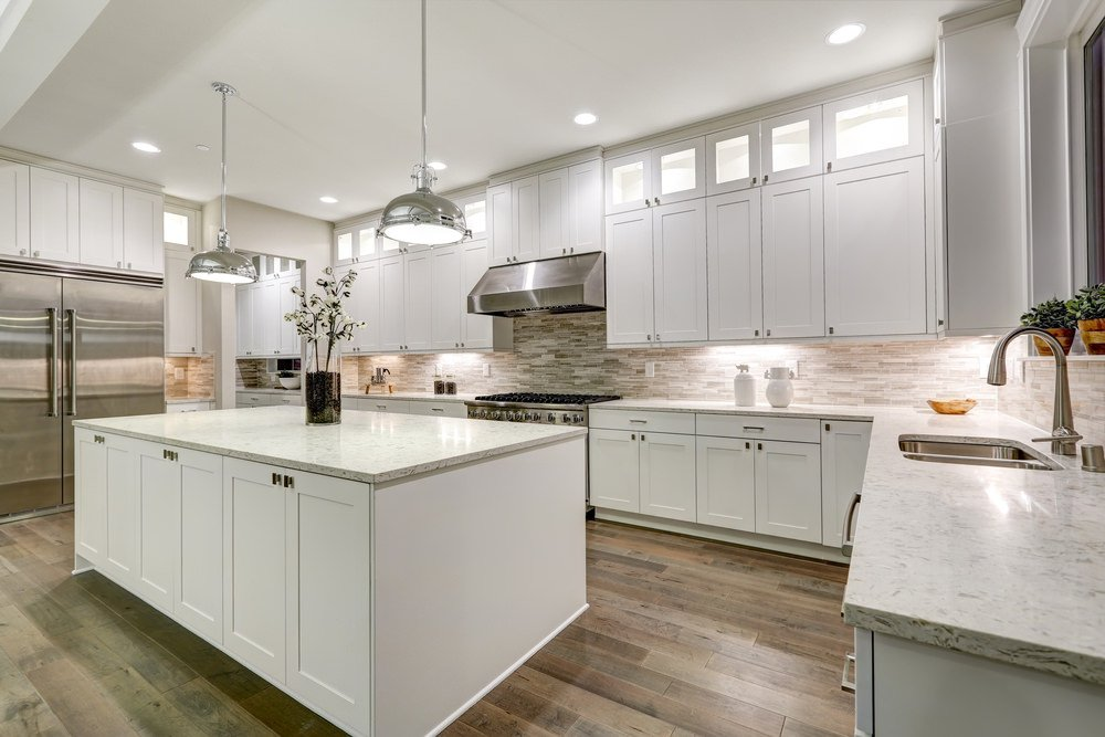 Large U-shaped kitchen boasting a large countertop set on the hardwood flooring. The counters are equipped with marble countertops. The area is lighted by the pendant and recessed lights.