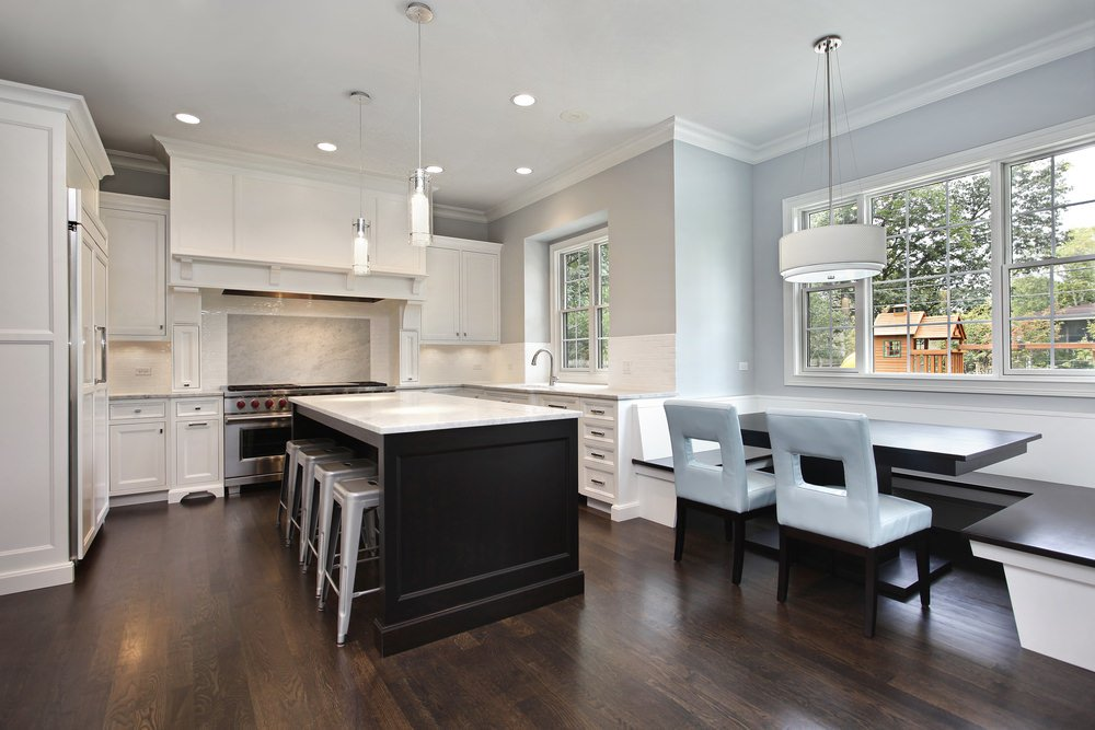 Modern kitchen with an island bar and breakfast nook offering a dark wood dining table surrounded with a U-shaped built-in bench and white chairs.