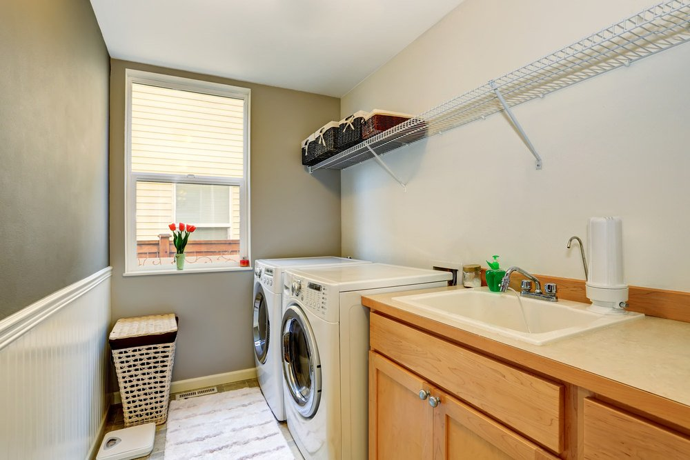 A small laundry room with a sink counter and walnut-finished cabinetry. There's a drying rack just above the sink and the washer.