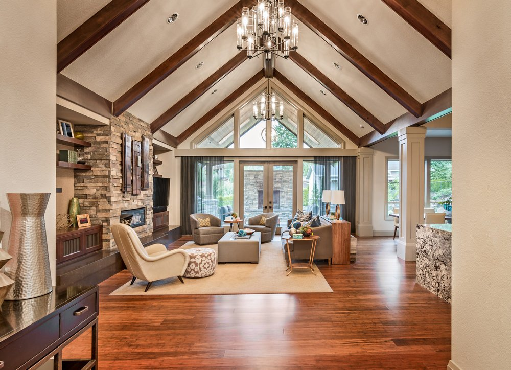 Spacious formal living room featuring a cozy living furniture set and a fireplace. The room also features rustic hardwood floors with a vaulted ceiling lighted by a modish chandelier.