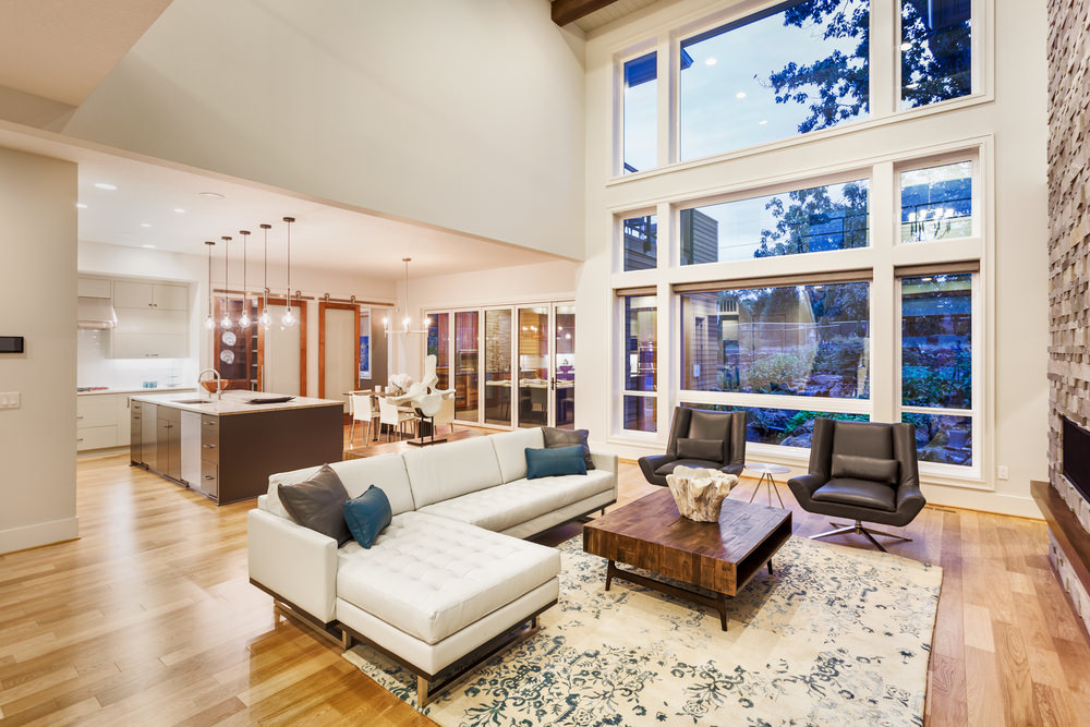 Modern great room featuring a set of cozy seats and a stylish center table, along with a brick-style fireplace. The room has a tall ceiling and glass windows.