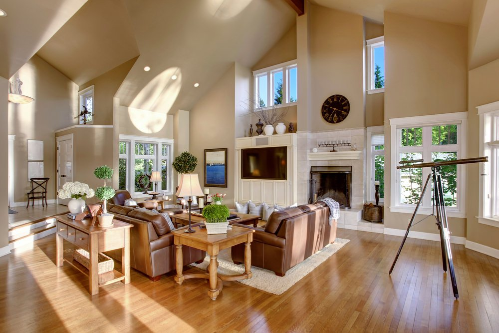Spacious living room featuring hardwood flooring, gray walls and a tall ceiling. The room offers brown leather seats and a fireplace.
