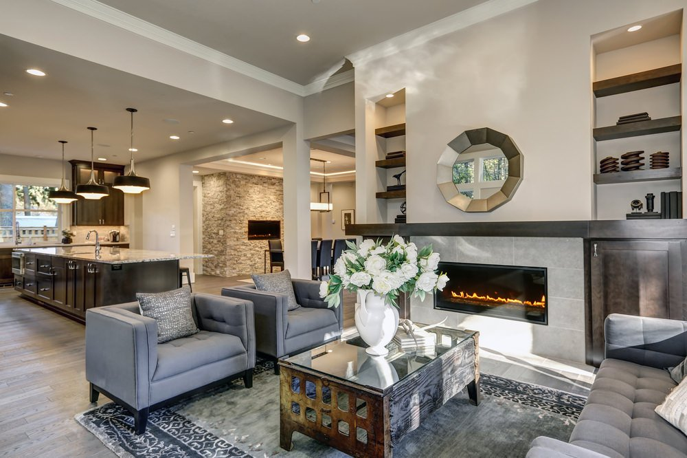 Modish living room boasting a stylish fireplace and sofa set. There's a lovely center table with white flowers in vase set on an enchanting gray rug.