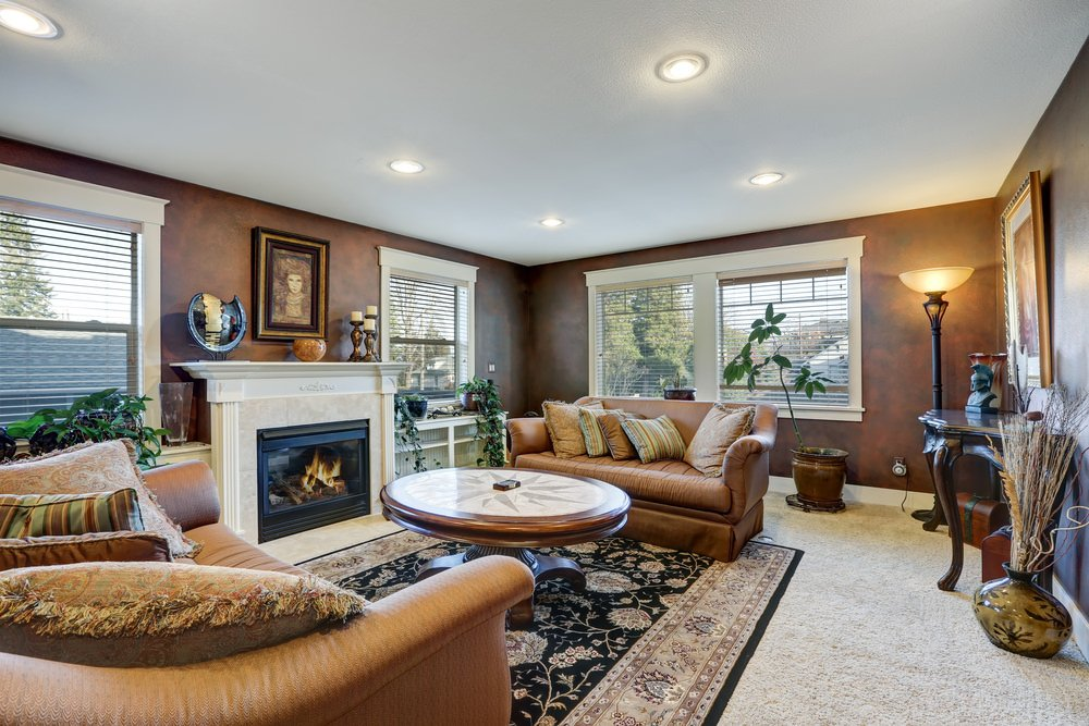 This living room boasts classy brown walls and a leather sofa set along with a charming center table. The room also features comfy carpet flooring and a fireplace.