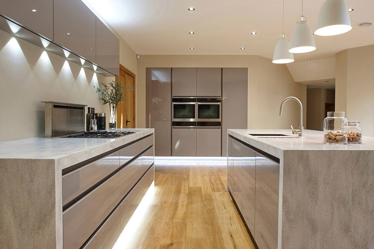 Modern kitchen featuring an island and a counter with the same waterfall-style countertop and are both set on the home's hardwood flooring.