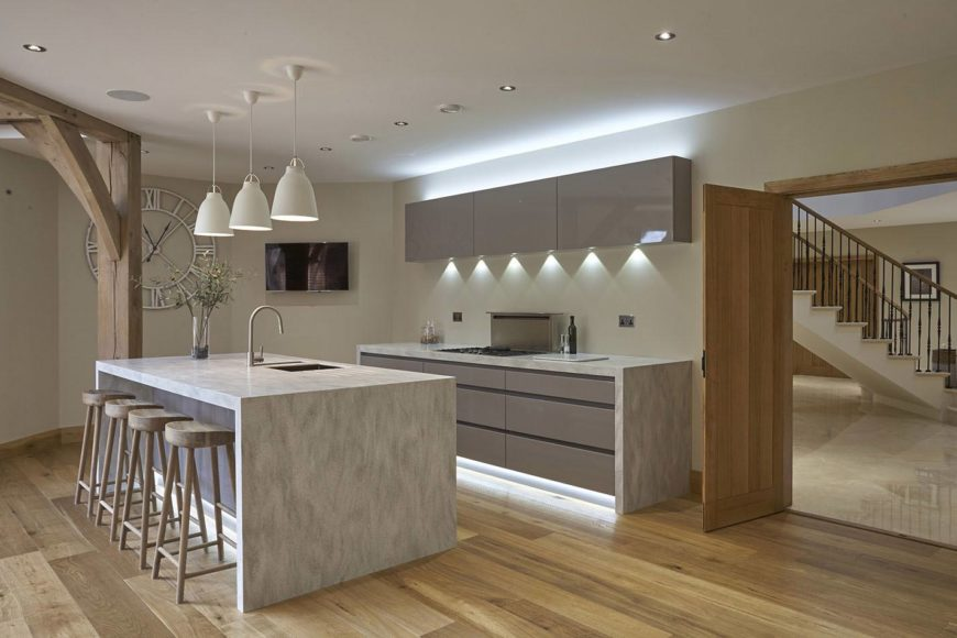 Stylish kitchen with a stone breakfast island aligned with wooden counter stools and lighted by white pendants. It is decorated with an oversized roman wall clock, gray cabinets with fabulous lights and gray marble countertops.