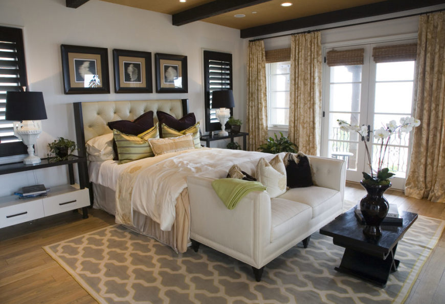 Magnificent master bedroom with white sofa and wood beams on ceiling.