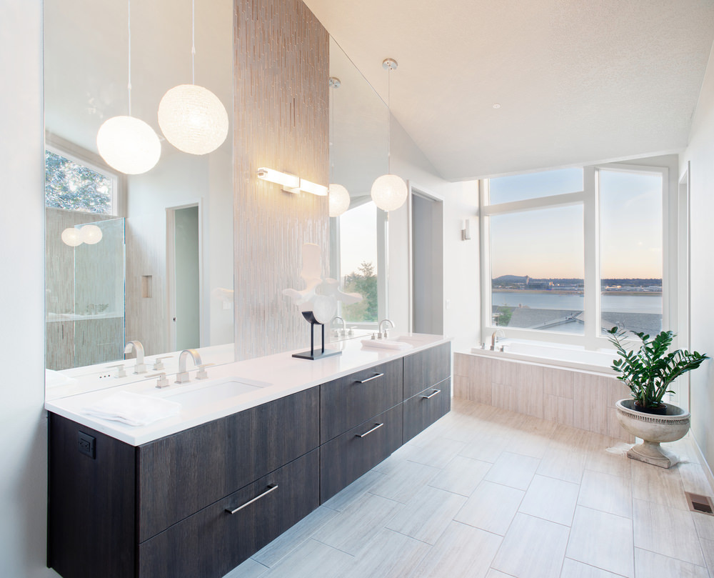 Bright master bedroom featuring two sinks lighted by pendant lights and a soaking tub near the glass window overlooking the beautiful surroundings.