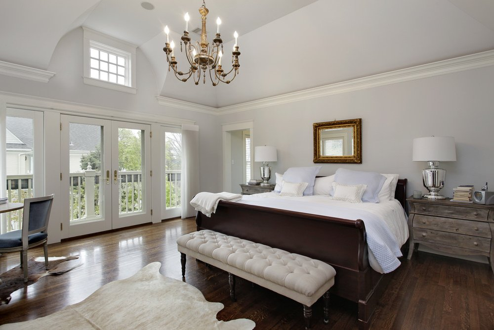 Large primary bedroom featuring hardwood floors and a couple of rustic side tables. There's a glamorous chandelier set on the room's high ceiling.