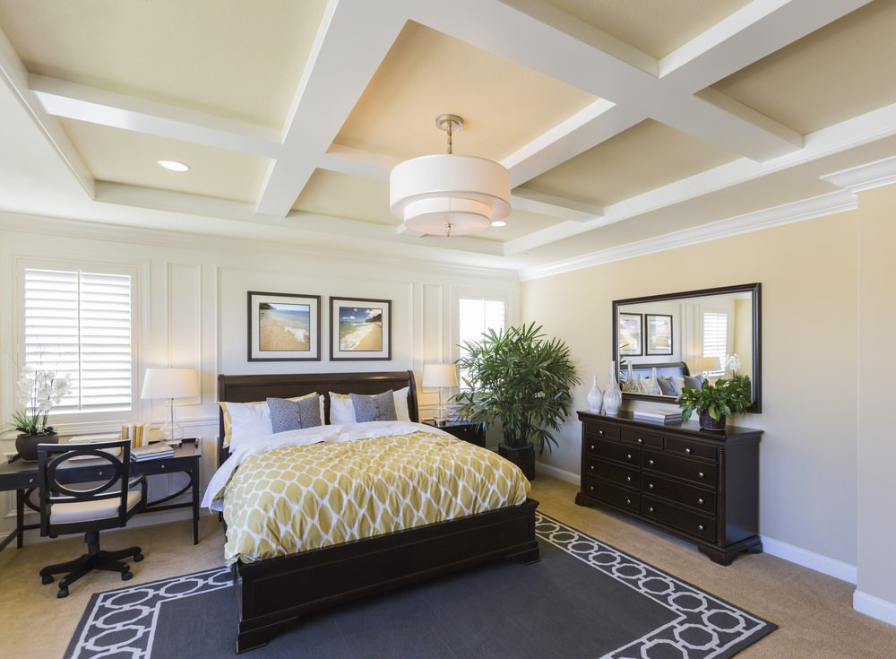 This primary bedroom boasts brown carpet flooring with a stylish rug on top. The room also boasts a beautiful coffered ceiling lighted by a pendant lighting.