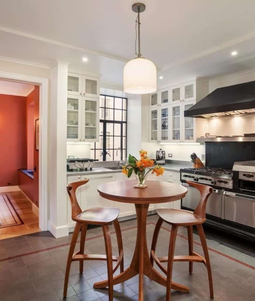 Small eat-in kitchen with white glass front cabinetry contrasted by a black range hood and a wooden dining set on the tiled flooring lighted by a glass pendant light.