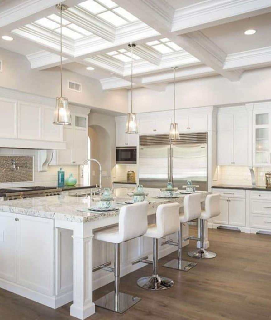 White kitchen illuminated by pendant lights that hung from the coffered ceiling fitted with recessed lighting and skylights which bring natural light in.