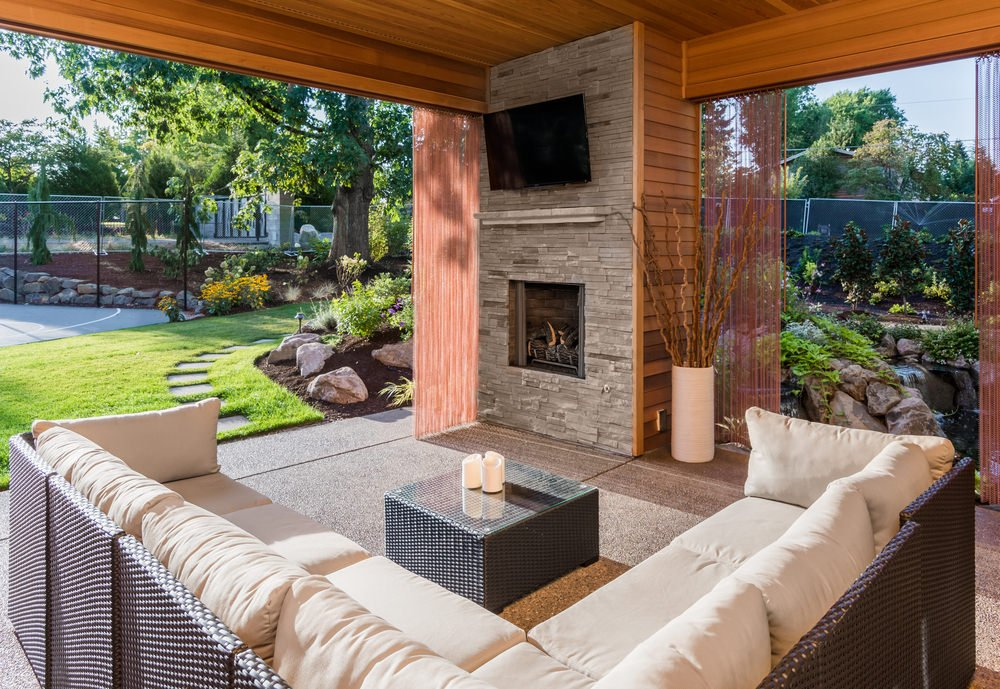 This patio offers an L-shape sofa set with cushion seats and foam backrests along with a rattan center table with a glass top. There's a fireplace and a TV above it.
