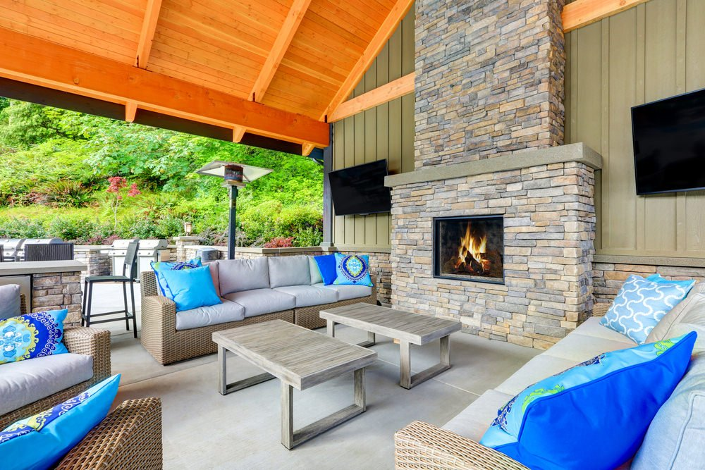 This classy patio boasts multiple rattan chairs and couches with cushion seats and foam backrests with two center table and a stylish fireplace.