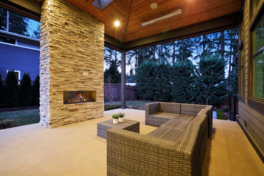 A classy patio featuring a set of rattan seats and center table in front of the fireplace lighted by warm white ceiling lights.