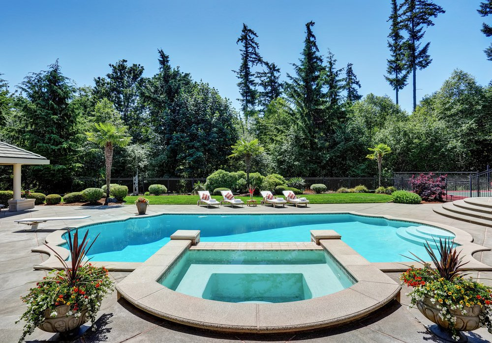 A fabulous swimming pool with astounding landscaping. There are lovely flowers on the side along with well maintained and manicured bushes and shrubs in the background.