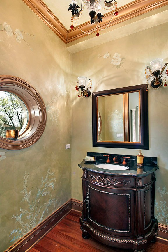Fancy powder room with copper crown molding, chandelier, deep wood vanity and round window. Gold-green wallpaper on the walls.