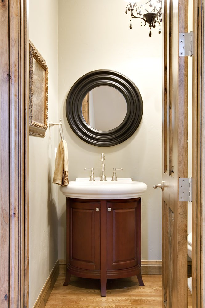 Nautical style powder room with wood base vanity and round mirror on wood flooring.