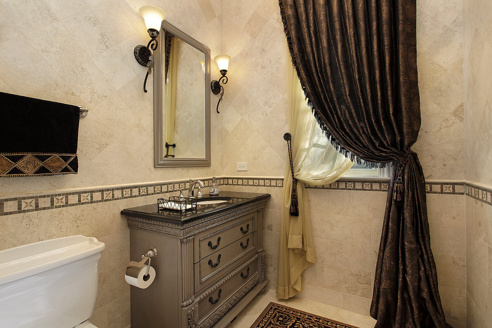 Powder room with converted dresser vanity with black surface. Large curtain covers the small window. Very elegant.