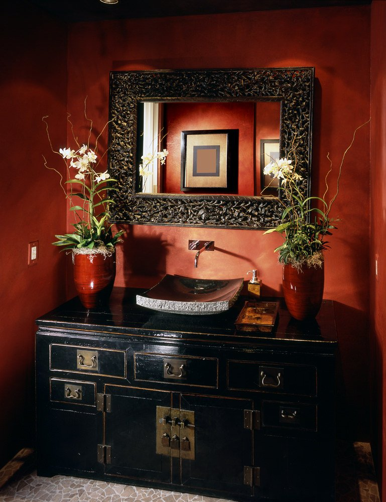Asian style powder room with chest-style vanity (black) vessel sink and large framed mirror with dark red walls.