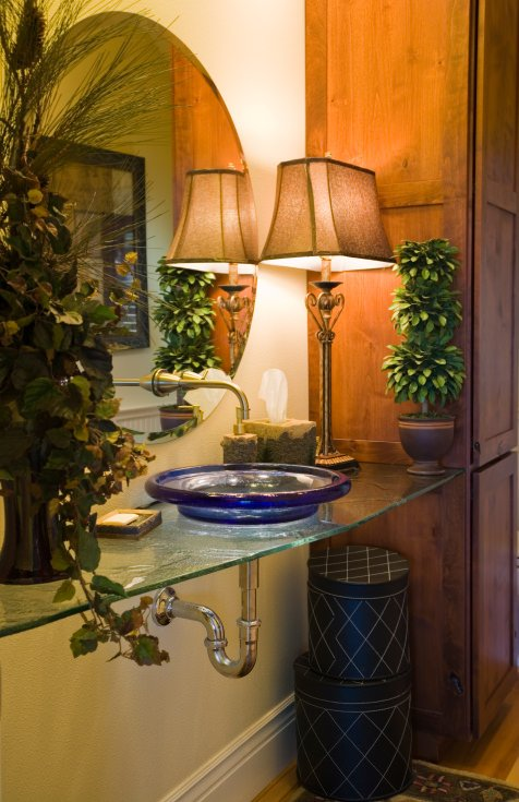 Stunning glass counter with blue glass vessel sink powder room.