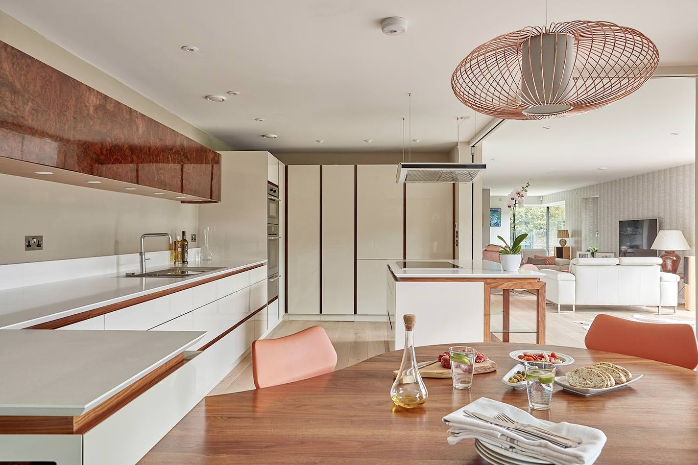 Spacious white kitchen with polished white cabinets and drawers, kitchen island, recessed lighting, and hardwood floors.