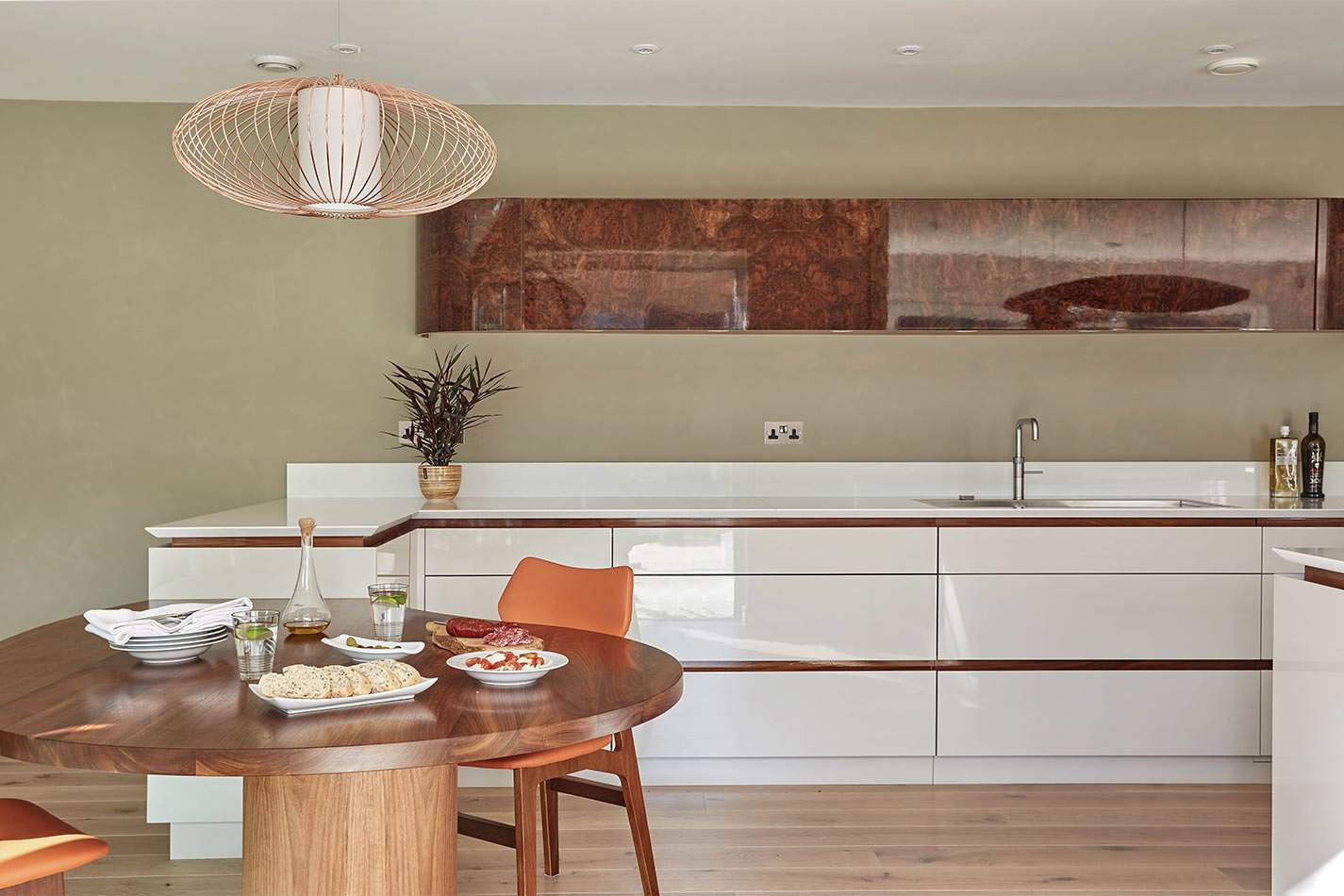 Single wall dine-in kitchen with polished white drawers, recessed lighting, and hardwood floors.