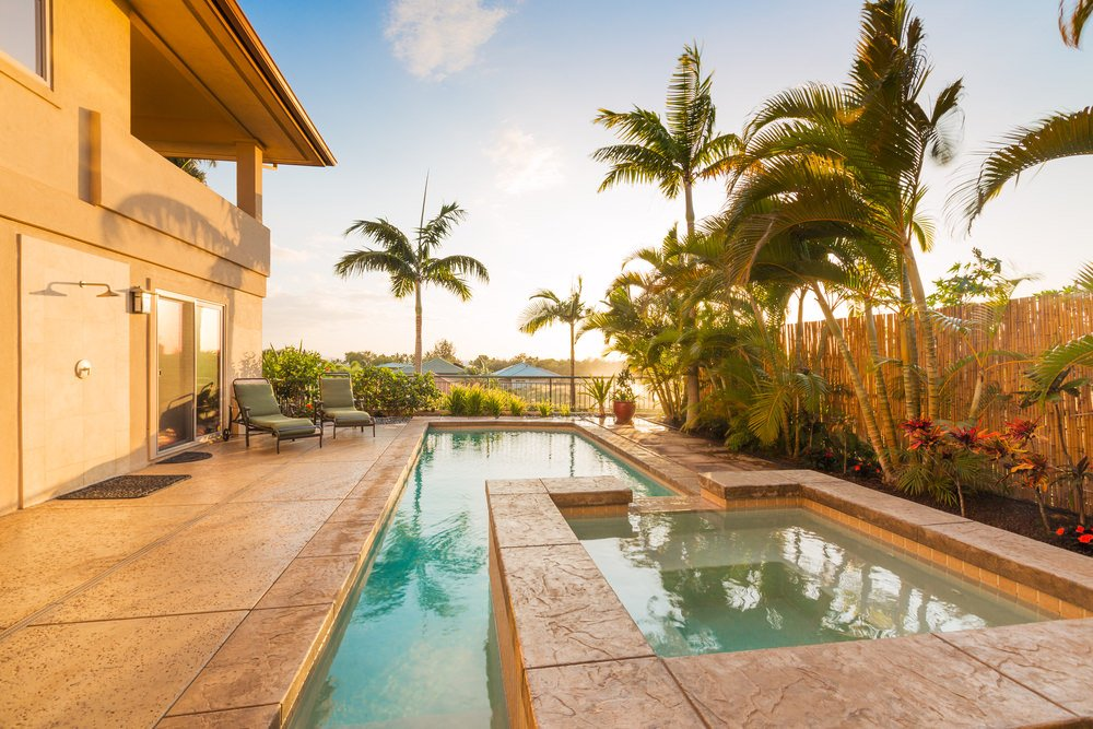 Concrete backyard features a swimming pool accented with palm trees. It includes a shower and seating area by the glass sliding doors.
