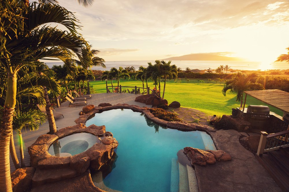 This backyard offers an expansive lush lawn and a freeform swimming pool with natural stones and an impressive scenic view.