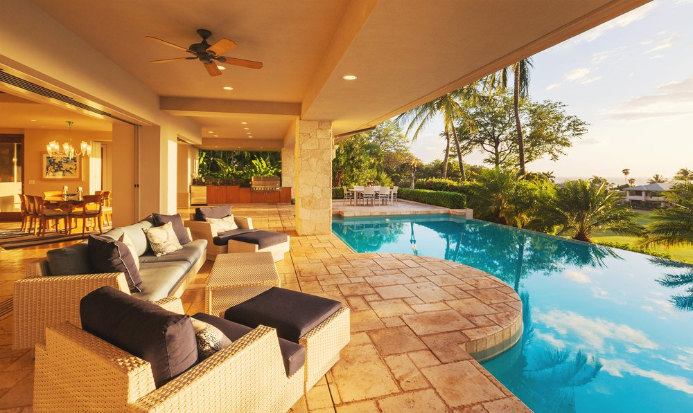Luxury house boasting a stunning infinity pool with stone tile deck and wicker seating.