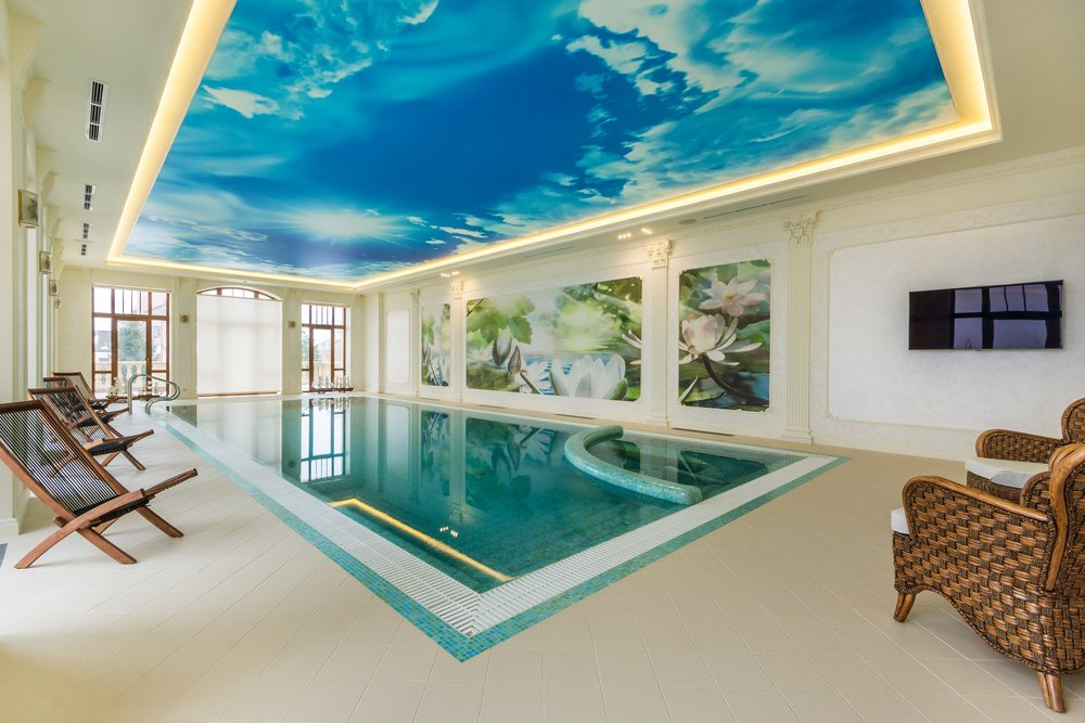 An indoor swimming pool decorated with a custom ceiling sky and floral wall arts in between Greek columns. It has a flat panel TV along with rattan armchairs and natural wood lounge chairs over tiled flooring.