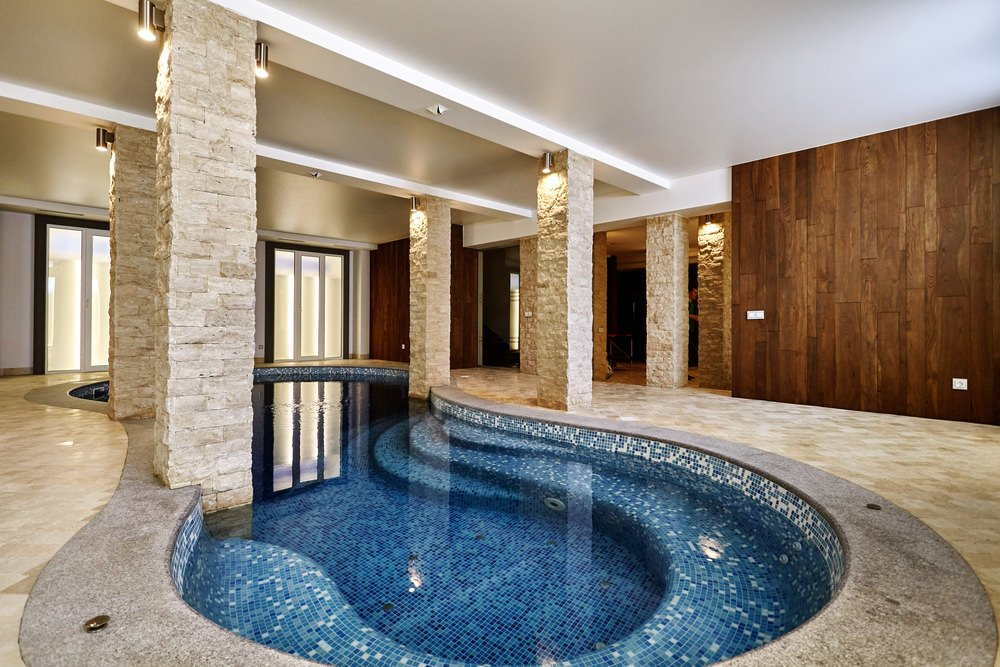 This house showcases an elegant curved swimming pool lined with stone brick columns that are illuminated by chrome sconces.