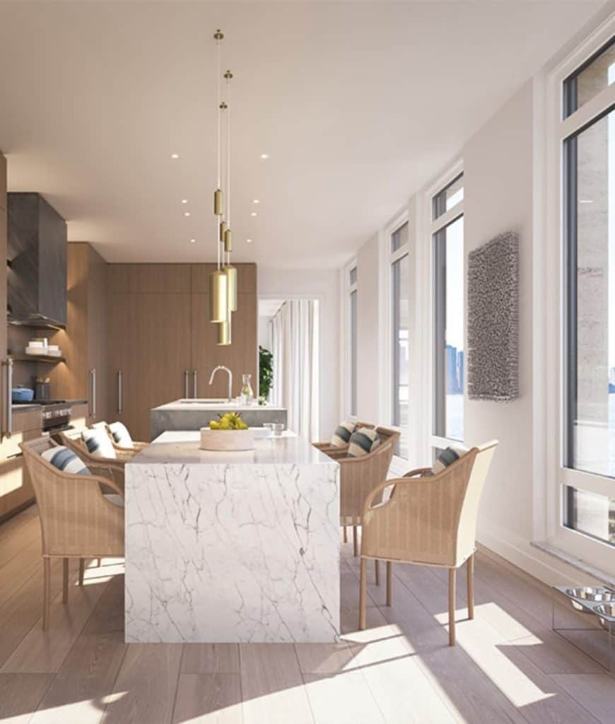 Natural light streams in through the glass paneled windows in this kitchen with a concrete island bar attached with a marble eating counter. It is lighted by brass pendants and pairedwith wicker chairs that are accented with striped pillows.