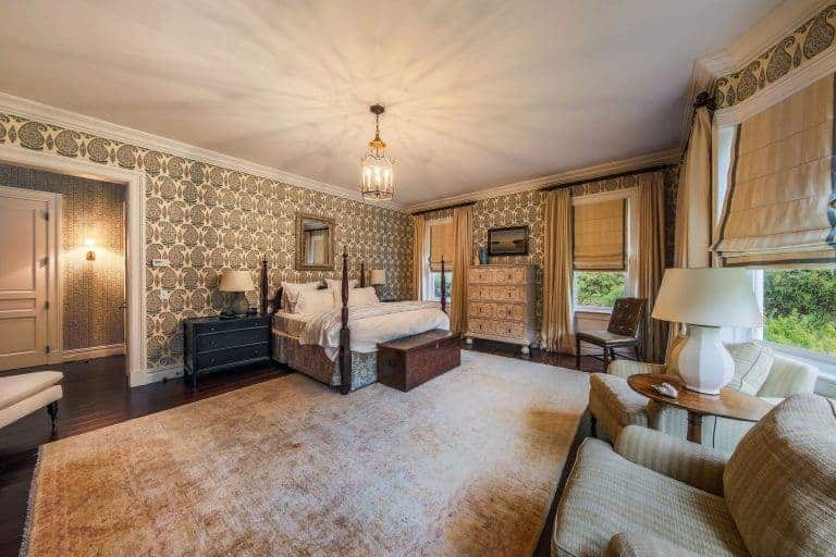 Warm traditional bedroom clad in lovely wallpaper that's framed with white moldings. It has a canopy bed and a seating area by the glazed windows dressed in beige roman shades.