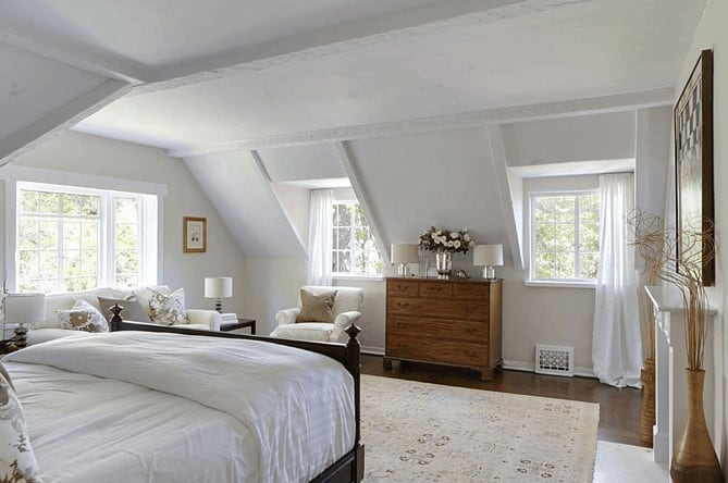 A wooden dresser that complements the hardwood flooring stands out in this traditional bedroom with comfy seats and vaulted ceiling.