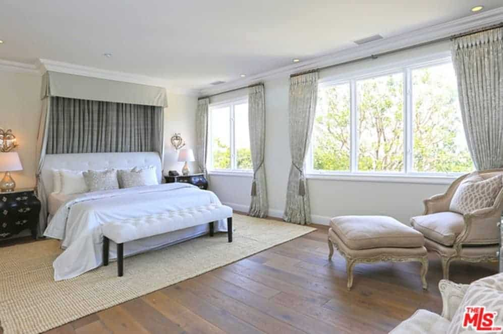 Bright traditional bedroom showcases a white bed with a canopy overhead and a tufted bench on its end. It is accompanied by a classy lounge chair and black nightstands topped with table lamps.