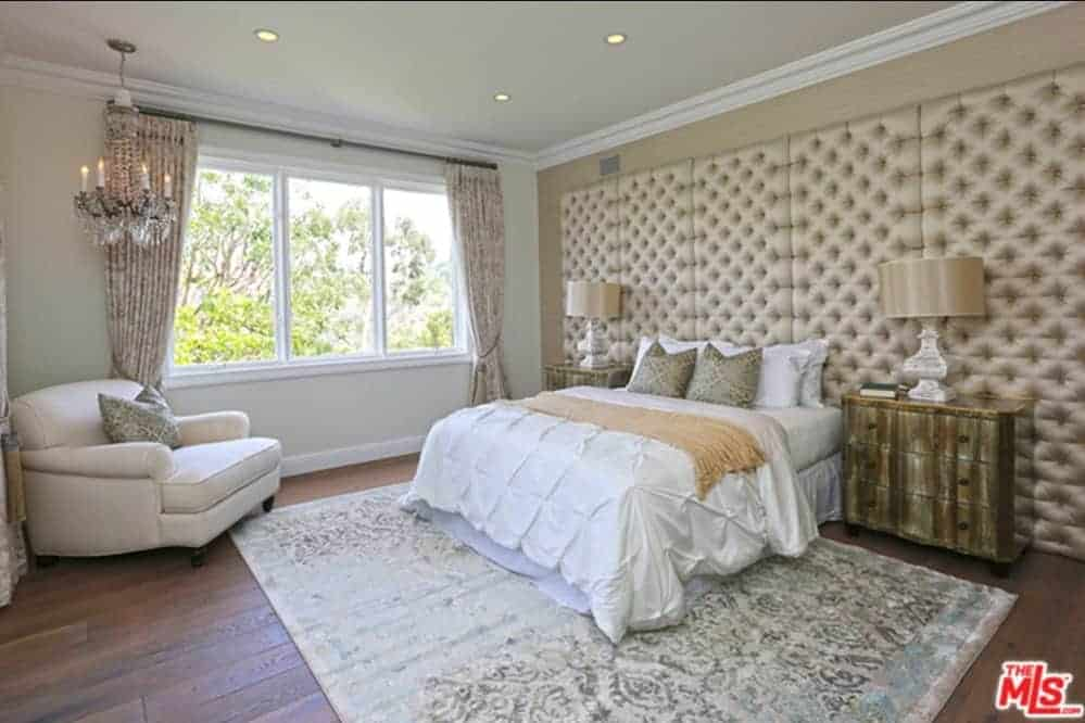Traditional bedroom features a white comfy bed with an oversized tufted headboard and a lounge chair by the glass paneled windows illuminated by a fancy chandelier.