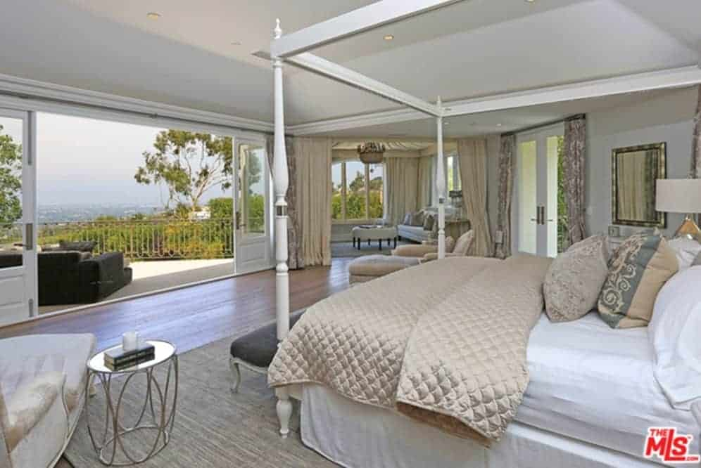 Spacious bedroom with wood plank flooring and a glazed double door that opens to the balcony overlooking the outdoor scenery.