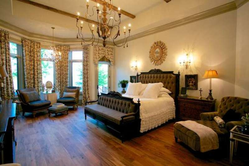 Warm bedroom decorated with a statement chandelier and a gold sunburst mirror mounted above the dark tufted bed. It has a matching lounge chair and a seating area by the full height windows.