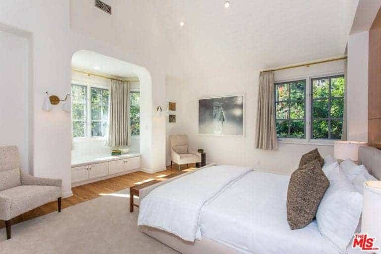 Traditional white bedroom features beige lounge chairs and a matching bed that faces the alcove seat nook by the framed window.