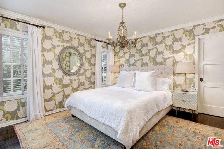 Classy bedroom clad in floral wallpaper offers a round mirror and tufted bed on a vintage rug illuminated by a candle chandelier and table lamps that sit on sleek nightstands.