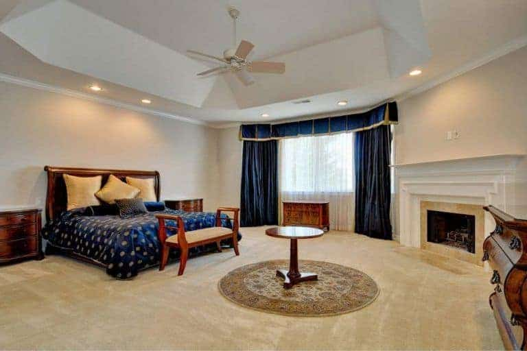 Traditional bedroom accented with classy blue drapes and valance that complement with the patterned bedding covering the wooden framed bed. There's a round coffee table in the middle surrounded by wooden furniture and white fireplace.