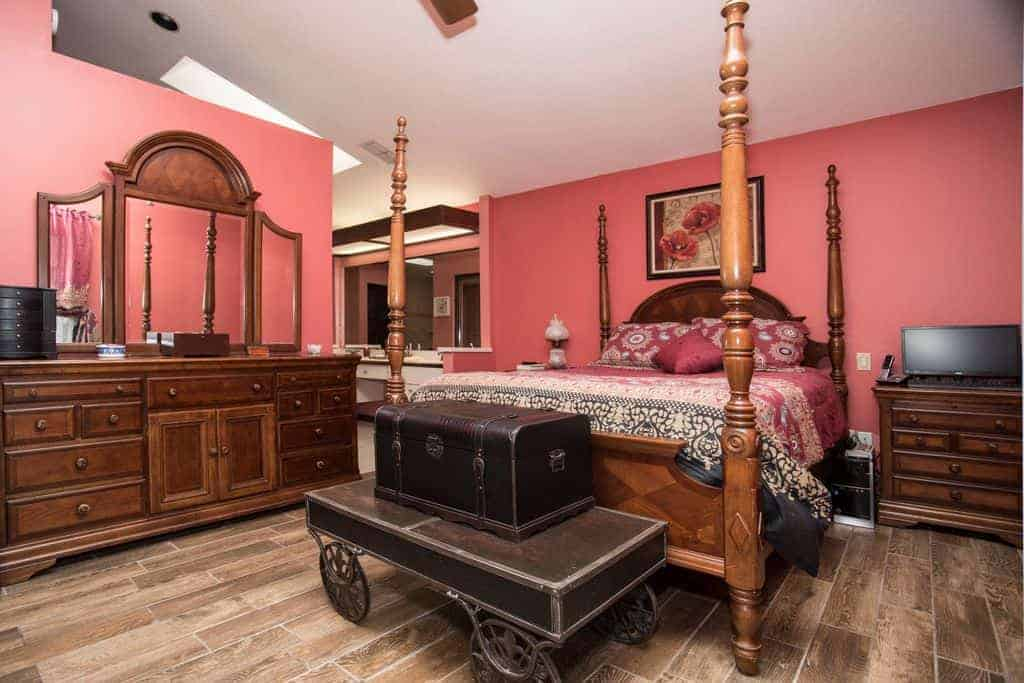 Traditional bedroom with a wooden four poster bed complementing with the nightstand and immense dresser that's topped with a three-panel mirror.