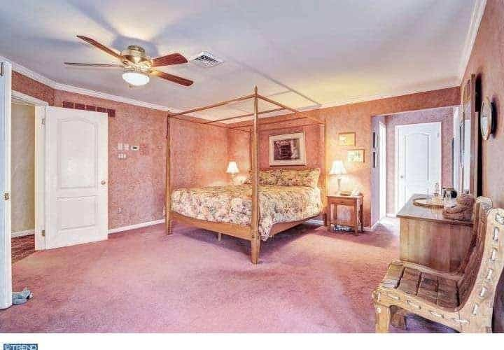 Pink bedroom showcases a wooden canopy bed dressed in floral bedding over carpet flooring. It is lighted by table lamps and a flush light attached to the ceiling fan.